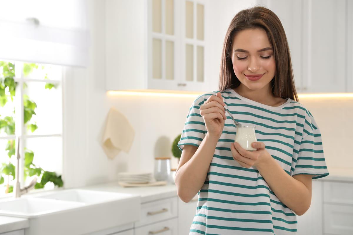 Donna a dieta che mangia lo yogurt